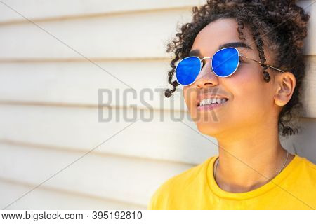 Girl teenager cool teen mixed race biracial African American female young woman wearing blue sunglasses and a yellow t-shirt on vacation smiling in summer sunshine