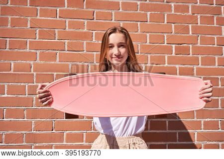 Young Woman Show Skateboard Deck. Pink Mockup. Sun Shade. High Quality Photo. Skatepark Equipment. T