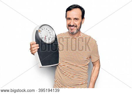 Middle age man controlling weight using weighting machine over isolated white background looking positive and happy standing and smiling with a confident smile showing teeth