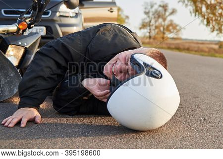 A Motorcyclist Lies On The Asphalt Near A Motorcycle And Car, The Theme Of Road Accidents.