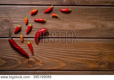 Pods Of Red And Yellow Chili Peppers Lying On A Dark Wooden Surface. Background For Spices And Seaso
