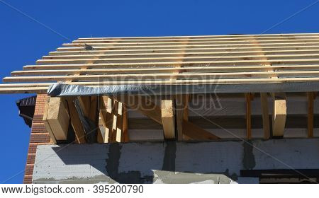 Unfinished Roofing Construction With A Close-up On Ceiling Joists, Wooden Rafters, Strutting Beams,