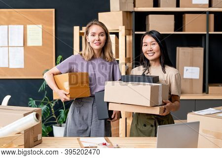 Two young female workers of online shop office holding packed orders while standing against shelf with boxes and noticeboard with documents