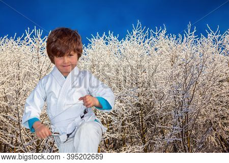 Handsome boy in judo uniform training for judo. The northern winter sun is low above the horizon. New Years is soon. Frosty snowy sunny day in the winter forest
