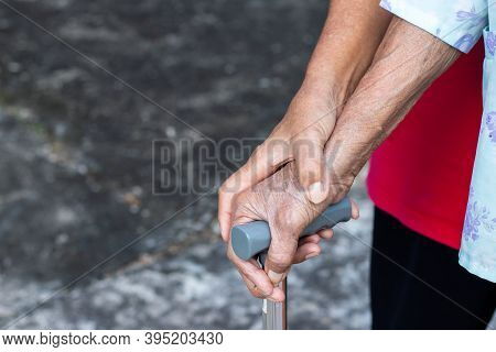 Asian Old Woman Standing With Her Hands On A Walking Stick With Daughter's Hand,hand Of Old Woman Ho