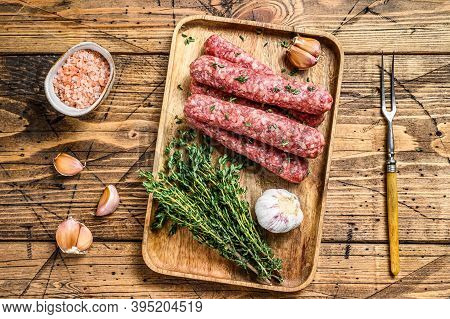 Homamade Raw Mince Meat Sausages On A Cutting Board. Wooden Background. Top View