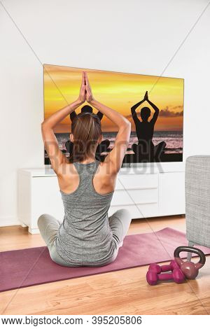 Home workout - woman exercising watching tv show on flat screen fitness program yoga exercising in living room. Yoga girl doing meditation exercise at home.