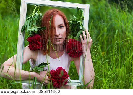 Redhead Caucasian Woman Holding A Picture Frame Decorated With Red Peony Flowers. Wedding Photozone