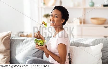 Healthy Nutrition Concept. Pretty Black Woman Eating Yummy Vegetable Salad On Sofa At Home, Panorama