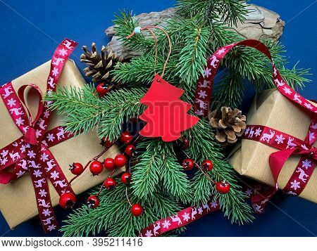 Christmas Tree Red Decoration, Gift Boxes With Red Ribbons, Spruce Branches With Red Berries And Pin