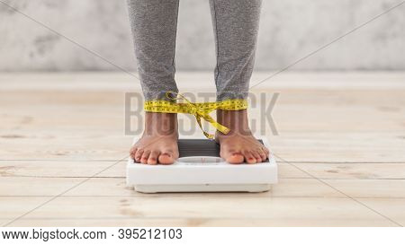 Unrecognizable Black Woman Standing On Scales, Checking Her Weight With Legs Tied By Tape Measure. C
