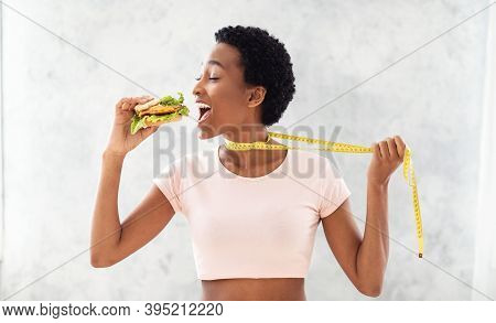Cheat Meal Or Diet Breakdown Concept. Black Lady Trying To Eat Unhealthy Burger, Pulling Herself Awa