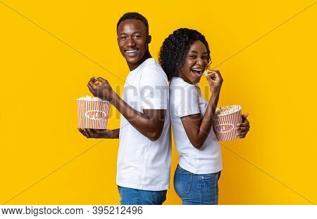 Carefree African American Man And Woman Eating Popcorn Over Yellow Studio Background, Standing Back