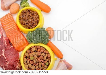 Raw Ingredients And Dry Pet Food On Whtie Background