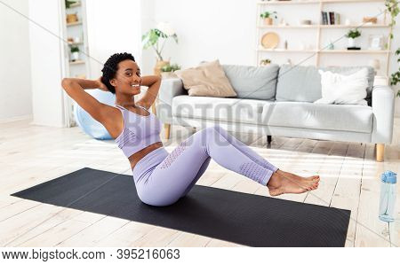 Home Workout Concept. Pretty Black Lady In Sportswear Doing Abs Exercises On Yoga Mat Indoors. Posit