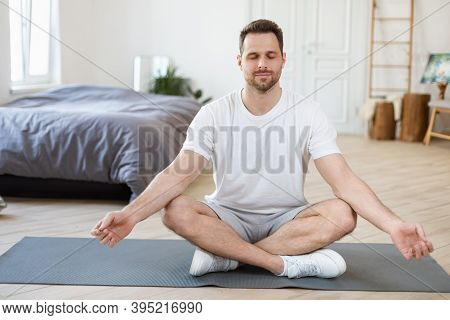 Stay Calm. Zen-like Man Meditating With Eyes Closed Sitting In Lotus Position Relaxing At Home. Morn