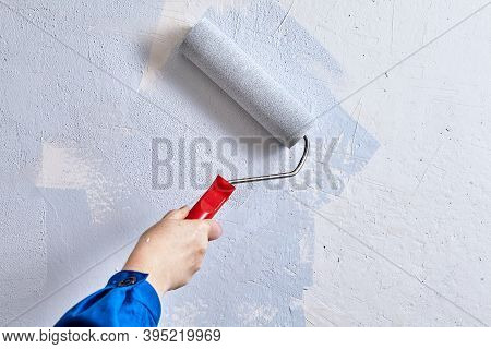 Home Painter Is Painting Walls With Paint Roller And Paints During Renovation.