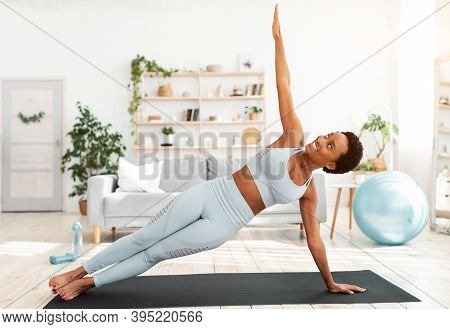 Attractive Fit Black Lady Standing In Side Plank On Sports Mat At Home. Motivated African American W