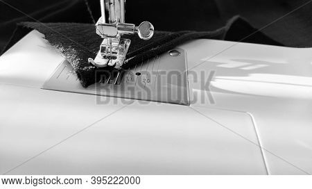 Sewing Process On A Modern Sewing Machine, Close-up. Sewing Machine Foot With A Needle. Dark Blue Fa