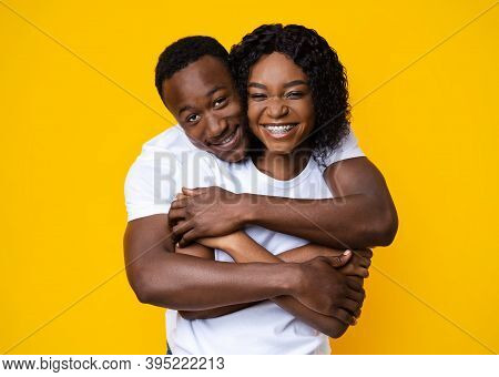 Loving Black Couple Cuddling Over Yellow Studio Background. Cheerful Young African American Man And
