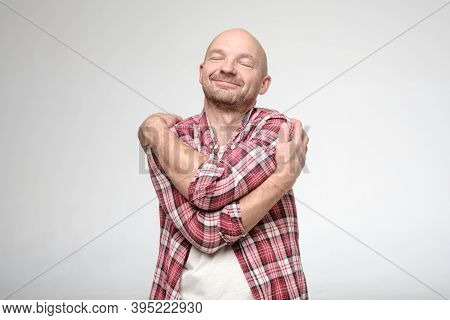 Handsome Man In A Plaid Shirt Hugs Himself And Dreams With His Eyes Closed. If You Feel Lonely, Hug