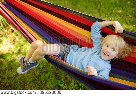 Cute Little Blond Caucasian Boy Relaxing And Having Fun In Multicolored Hammock In Backyard Or Outdo