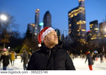 Handsome Man In Santa Claus Hat Skating On Rink Central Park On Christmas Eve. Crowds Local People A