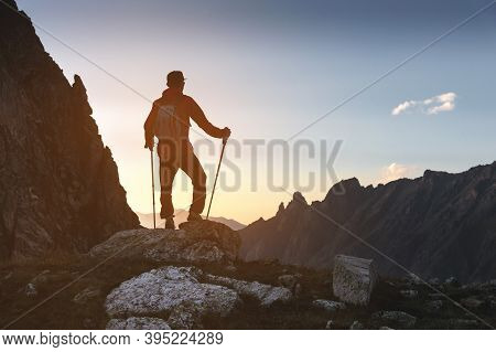A Silhouette Of A Man In A Cap With Sunglasses And A Backpack Stands High In The Mountains On Top Of