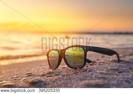 Sunglasses Lie In The Sand On The Sea Coast At Sunset. Holidays And Vacations By The Ocean