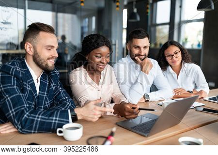 Black Businesswoman Presenting Her Project On Laptop To Colleagues Brainstorming Business Idea Toget