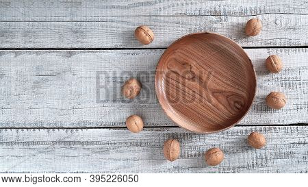 On A Wooden Background - A Platter Of Elm Wood, And Around It Are Many Walnuts