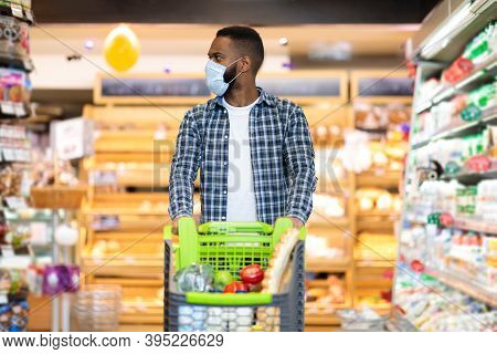 Black Man With Shopping Cart In Supermarket Buying Groceries Food Products Walking Along The Aisle A