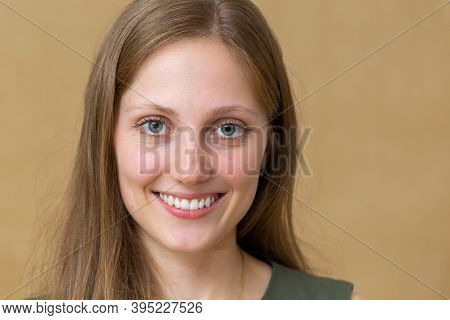 Happy Young Blonde Woman Laughing In Studio In Close Up