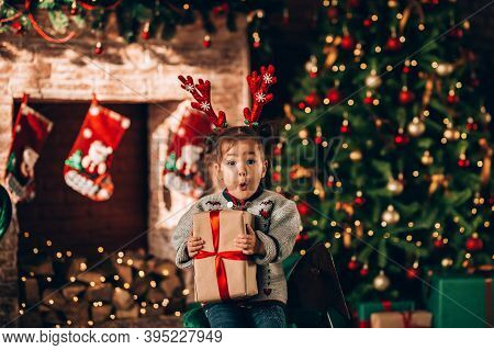Little Girl Sitting In Front Of A Decorated Christmas Tree. Against The Background Of A Christmas Tr