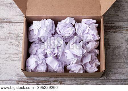 Crumpled Paper Balls Filler In Cardboard Box. Opened Parcel With Filler On Wooden Floor.