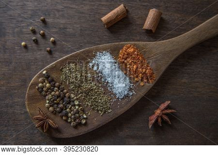 Spices In A Wooden Spoon. Set Of Spices On A Dark Wooden Background. Indian Food. Pepper, Salt, Clov