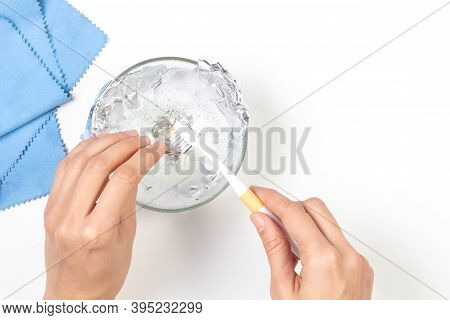 Woman Hands Cleaning Silver Jewelry At Home. Top View