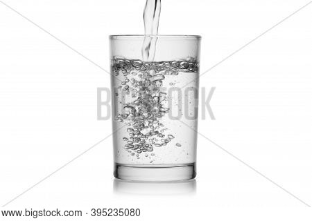 Splash Jet Of Water Pours In Glass With Bubbles Isolated On A White Background Without Glare. Reflec