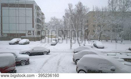 Winter Is Here. Snowfall In The City. White Snow Covered Cars, Parked On Road Near Residential Build