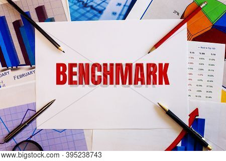 The Word Benchmark Is Written On A White Background Near Colored Graphs, Pens And Pencils. Business