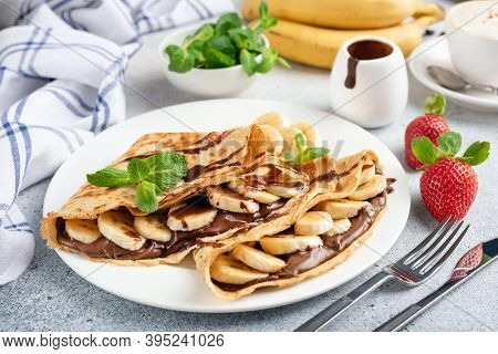 Crepes Filled With Chocolate Nut Spread And Banana Slices On White Plate. Dessert French Crepes Or R