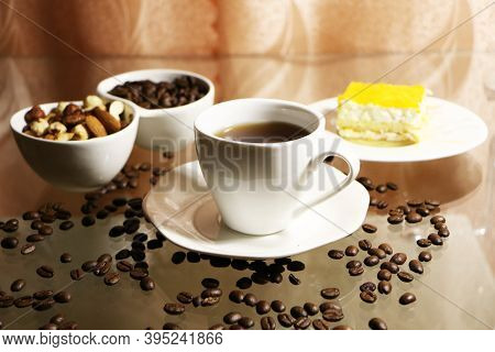 Cup Of Coffee And Coffee Beans On A Glass Table. The Concept Of Home Comfort And Warmth. On The Tabl
