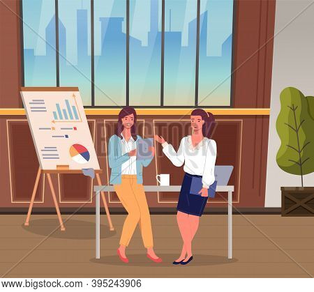 Two Businesswomen Talking In The Office. Women Leaning At Table With Computer And Cup. Flipchart Wit