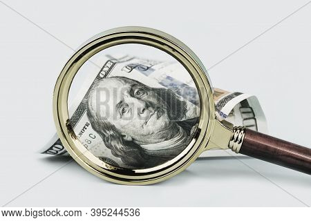 One Hundred Dollars Note Under Magnifying Glass On Grey Background. Finance Markets. Investments Loa