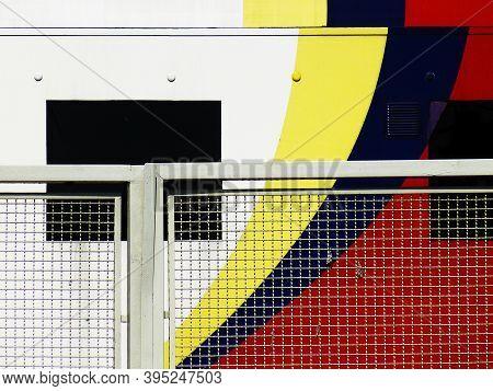 Detalle De Puerta Con Reja, Ventanas Y Decoración De Colores Primarios. Detail Of Door With Bars, Wi