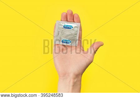 Man's Hand Holding Condom Over A Yellow Background, Give Condom Safe Sex Concept On Isolated Backgro