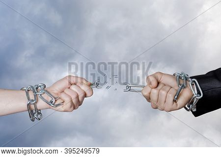 Dependency Break Concept. Hands Break The Chain Against The Background Of The Sky.