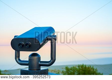 Binoculars installed on observation platform on beach against cloudless sundown sky and calm sea