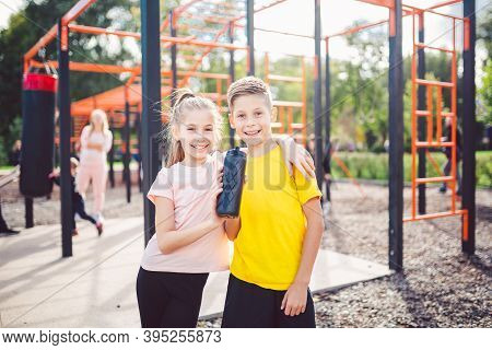 Teens Children And Sports Theme. Two Kids Athletes Twins Rest And Replenish Their Thirst During Work