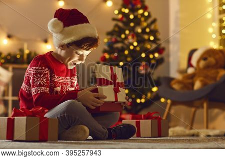 Cheerful Boy Feeling Happy After Opening Festive Gift Box With Christmas Presents Inside